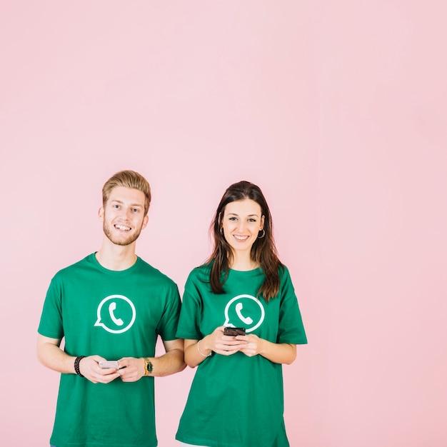Portrait d'un couple heureux en vert whatsapp t-shirt tenant un smartphone Photo gratuit