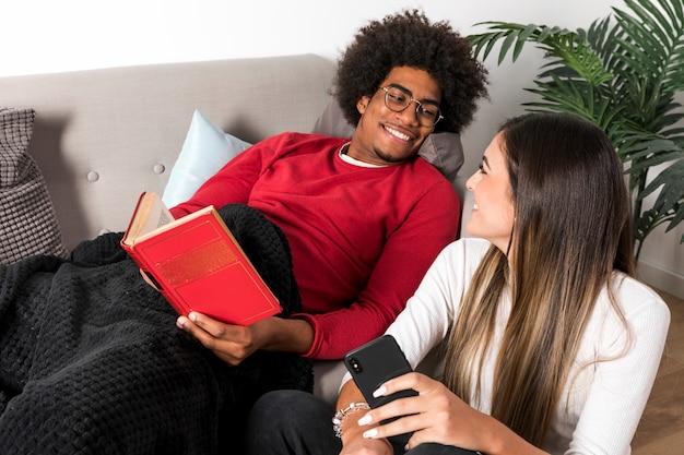 Portrait de couple interracial lisant ensemble Photo gratuit