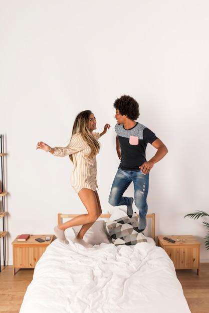 Portrait, de, couple interracial, sauter lit Photo gratuit