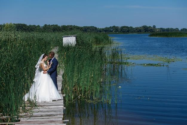Portrait D'un Couple De Mariage Marchant Sur Un Pont En Bois Près Du Lac. Mariée Et Le Marié Heureux Embrasse Doucement à L'extérieur. Jeune Couple Amoureux Enjoing Mutuellement Dans La Nature Près De La Rivière. Photo Premium