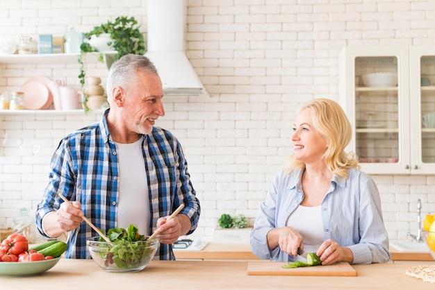 Portrait d'un couple de personnes âgées préparant la salade dans la cuisine Photo gratuit