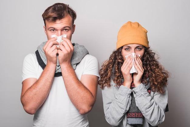 Portrait De Couple Se Moucher Avec Du Papier De Soie Sur Fond Gris Photo Premium