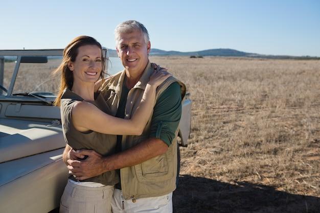 Portrait d'un couple souriant en véhicule sur le terrain Photo gratuit
