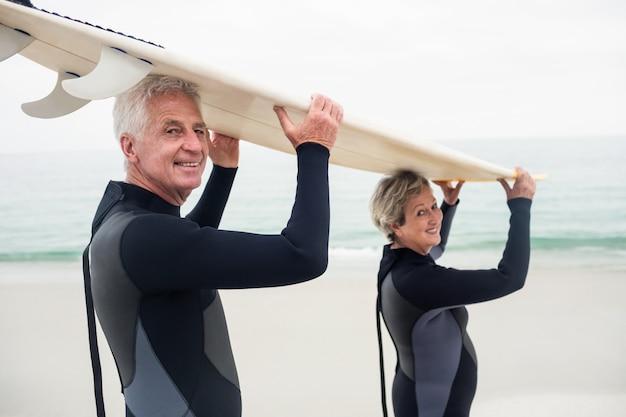 Portrait, de, couples aînés, dans, wetsuit, porter, planche surf, sur, tête Photo Premium