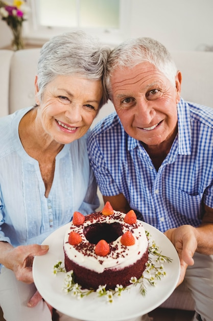 Portrait, de, couples aînés, tenant gâteau, et, sourire, dans, salle de séjour Photo Premium