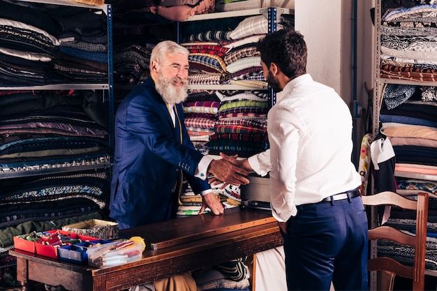Portrait d'un créateur de mode senior souriant, serrant la main du client dans son magasin Photo gratuit