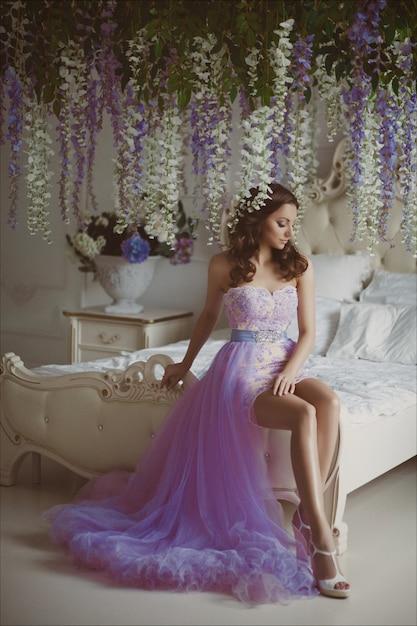 Portrait créatif d'une femme fashion avec des fleurs dans une magnifique robe romantique longue rose Photo Premium