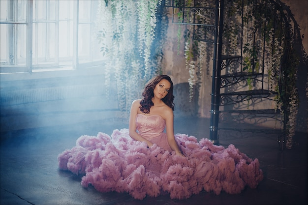 Portrait créatif d'une femme de la mode dans une magnifique robe romantique longue rose Photo Premium