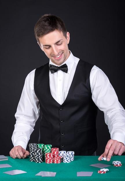 Portrait d'un croupier heureux tient des cartes à jouer. Photo Premium
