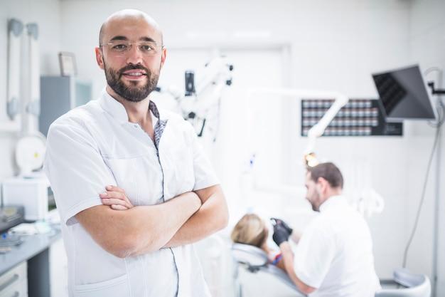 Portrait d'un dentiste avec les mains jointes Photo gratuit