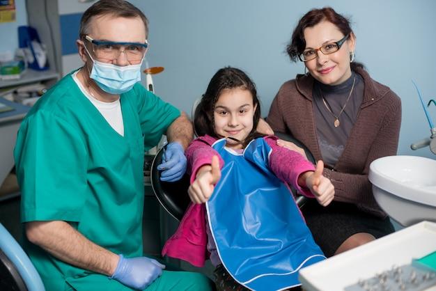 Portrait De Dentiste Pédiatrique Senior Et Fille Avec Sa Mère Lors De La Première Visite Dentaire Au Cabinet Dentaire. Le Jeune Patient Sourit, Montrant Les Pouces Vers Le Haut. Concept De Dentisterie, Médecine Et Soins De Santé Photo Premium
