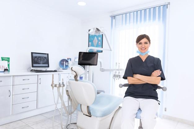 Portrait d'un dentiste souriant confiant en clinique avec machine et équipement Photo gratuit