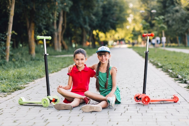 Portrait de deux amies assis sur le trottoir avec leur trottinette dans le parc Photo gratuit