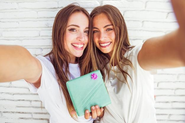 Portrait de deux amies joyeuses avec boite cadeau Photo gratuit