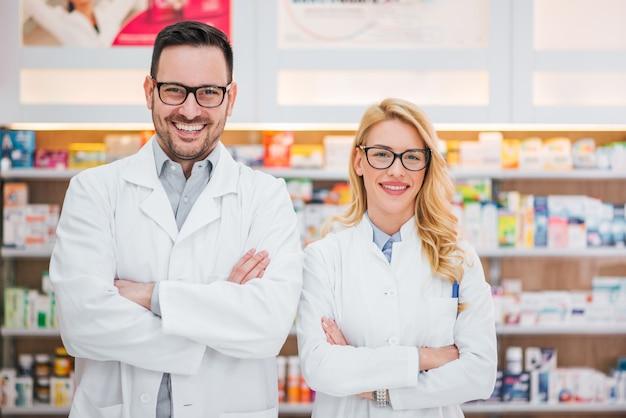 Portrait de deux beaux jeunes pharmaciens sur le lieu de travail. Photo Premium