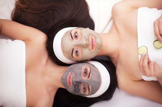Portrait, de, deux, belles filles, à, crème visage, sur, leurs, visage, et, mensonge, face à face, sur, les, sourire Photo Premium