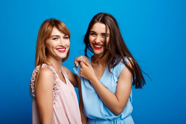 Portrait De Deux Belles Filles Sur Mur Bleu Photo gratuit