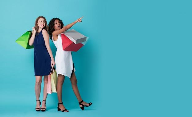 Portrait, de, deux, excité, main jeune femme, tenue, sac à provisions, et, son, doigt pointage, copie, espace, sur, arrière-plan bleu Photo Premium