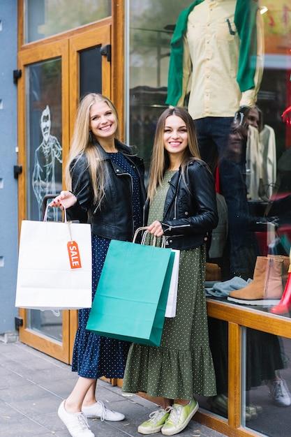 Portrait, deux, femmes, debout, dehors, magasin, tenue, coloré, sacs provisions Photo gratuit