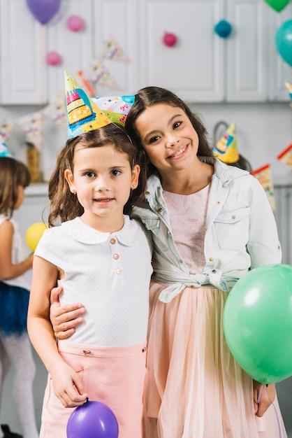 Portrait de deux filles debout avec des ballons colorés Photo gratuit