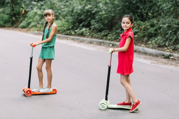 Portrait, deux, filles, debout, pousser, scooter, rue Photo gratuit