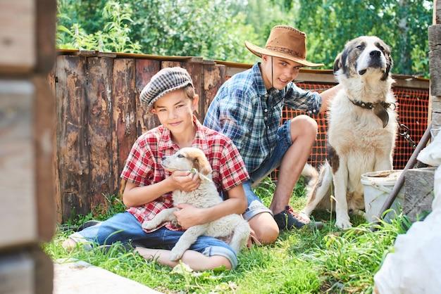 Portrait De Deux Frères Assis à La Place Avec Des Chiens Sur L'herbe Dans Le Village Photo Premium
