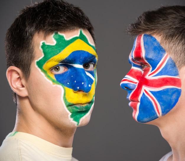 Portrait de deux hommes avec des drapeaux peints sur leurs visages. Photo Premium