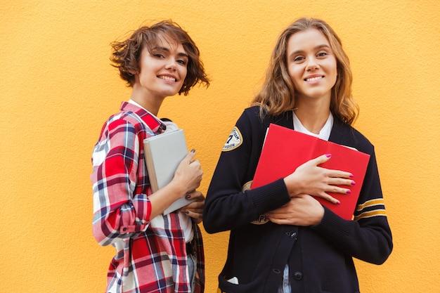 Portrait De Deux Jeunes Adolescentes Avec Des Livres Debout Photo gratuit