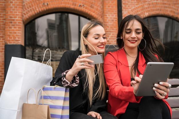 Portrait De Deux Jeunes Amis, Faire Du Shopping En Ligne Avec Carte De Crédit Et Tablette Numérique Assis à L'extérieur. Concept D'amitié Et De Style De Vie. Photo Premium