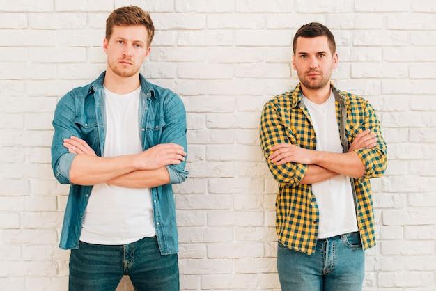 Portrait de deux jeunes amis de sexe masculin avec les bras croisés en regardant la caméra Photo gratuit