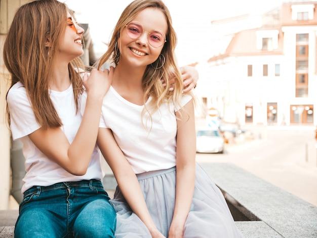 Portrait De Deux Jeunes Belles Filles Blondes Souriantes Hipster Dans Des Vêtements De T-shirt Blanc à La Mode D'été. . Modèles Positifs S'amusant Avec Des Lunettes De Soleil. Photo gratuit