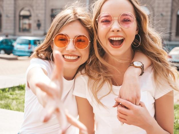 Portrait De Deux Jeunes Belles Filles Blondes Souriantes Hipster Dans Des Vêtements De T-shirt Blanc à La Mode D'été. Photo gratuit