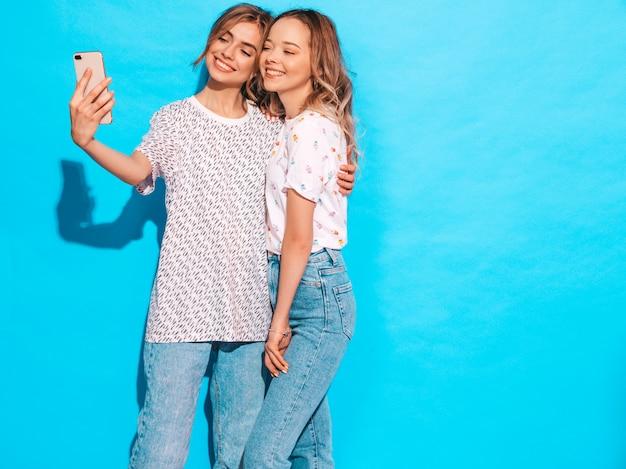 Portrait De Deux Jeunes Femmes Blondes Souriantes élégantes. Filles Vêtues De Vêtements D'été Hipster. Modèles Positifs Faisant Selfie Sur Smartphone Près Du Mur Bleu En Studio Photo gratuit