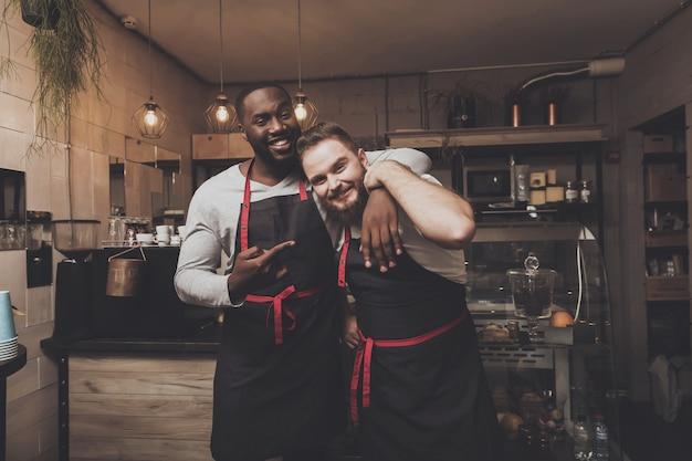 Portrait de deux jeunes hommes barista à l'espace de travail Photo Premium