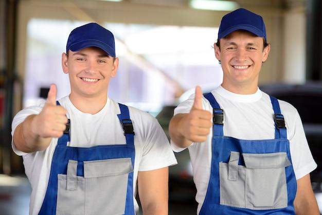 Portrait De Deux Mécaniciens En Réparation Automobile Photo Premium