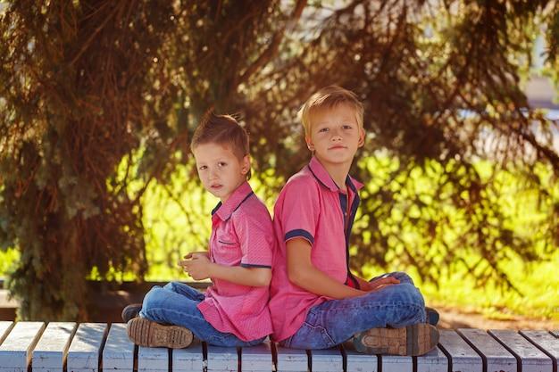 Portrait deux petits garçons jouant à des jeux sur téléphone portable sous le soleil Photo Premium