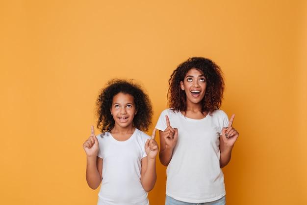 Portrait De Deux Soeurs Afro-américaines Joyeuses, Pointant Les Doigts Photo gratuit