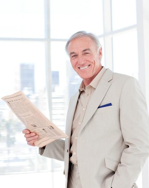 Portrait d'un directeur souriant lisant un journal Photo Premium
