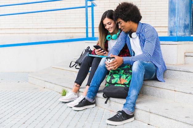 Portrait de divers adolescents et étudiantes assis sur les marches à l'aide d'un téléphone portable Photo gratuit
