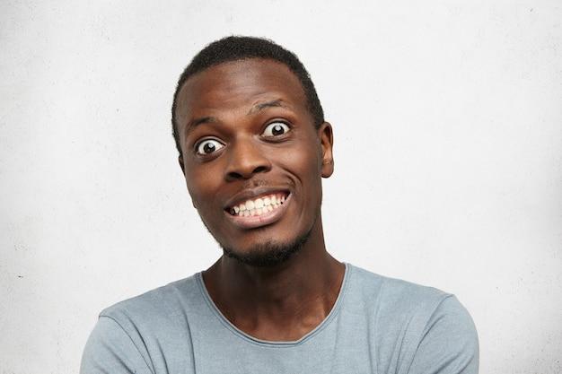 Portrait De Drôle De Jeune Homme Africain Terrifié, Bougeant Les Yeux, Montrant Les Dents Photo gratuit