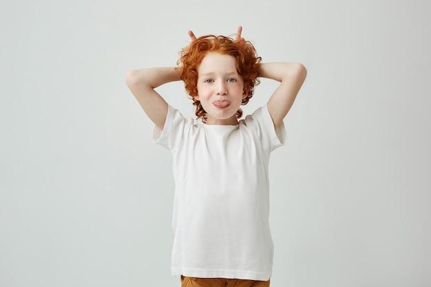 Portrait De Drôle Petit Garçon Rousse Avec Des Taches De Rousseur S'amuser à L'intérieur, Sortir Sa Langue Et Faire Des Cornes Avec Les Doigts. Photo gratuit