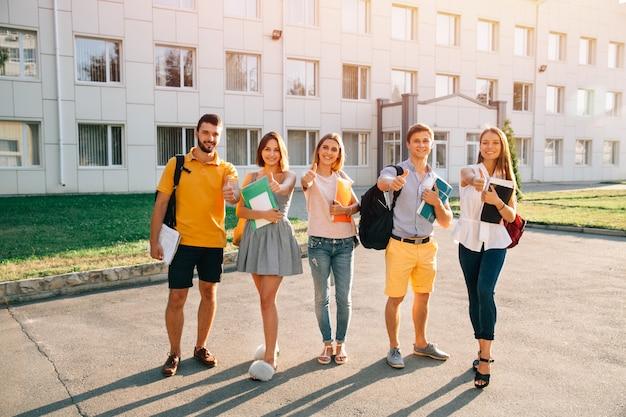 Portrait du groupe d'étudiants heureux en tenue décontractée avec des livres montrant les pouces vers le haut Photo gratuit