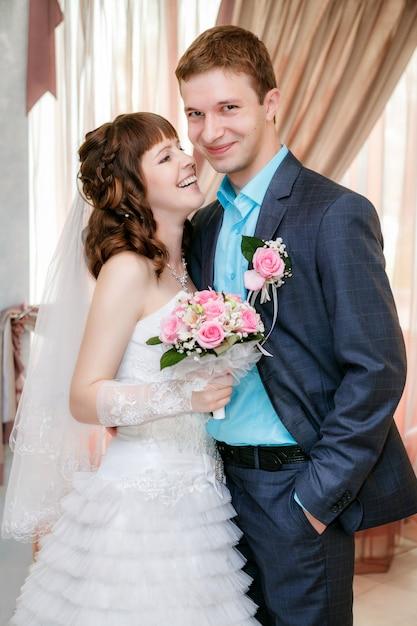 Portrait du marié et de la mariée près d'une fenêtre Photo Premium