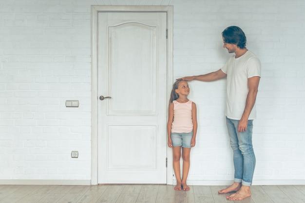 Portrait du père mesurant la hauteur de sa fille mignonne. Photo Premium