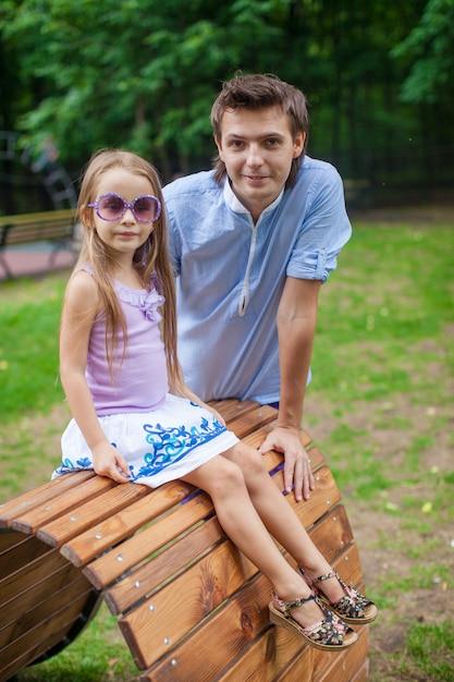 Portrait du père avec sa fille assise sur le lit de la planche de bois dans le parc Photo Premium
