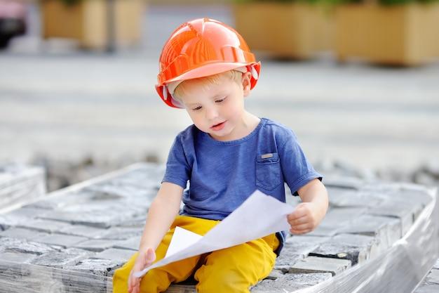 Portrait du petit constructeur en casque lire le dessin de construction. Photo Premium