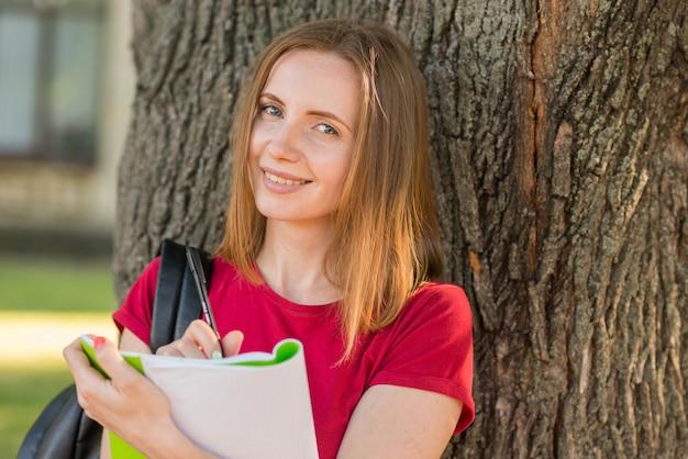 Portrait d'écolière appuyé contre un arbre Photo gratuit
