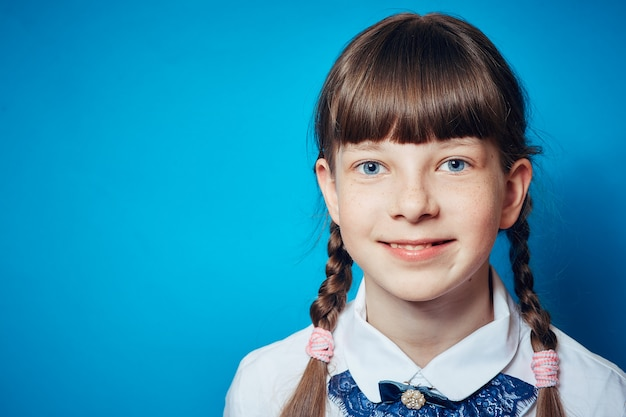 Portrait d'une écolière sur fond bleu Photo Premium