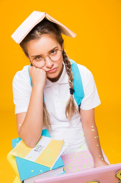 Portrait d'écolière sur fond jaune Photo gratuit