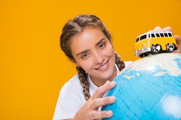 Portrait d'écolière avec un globe Photo gratuit